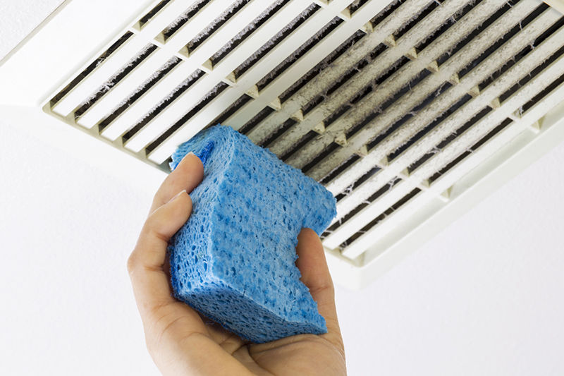 Close up horizontal photo of female hand cleaning dirty bathroom fan vent cover with blue sponge